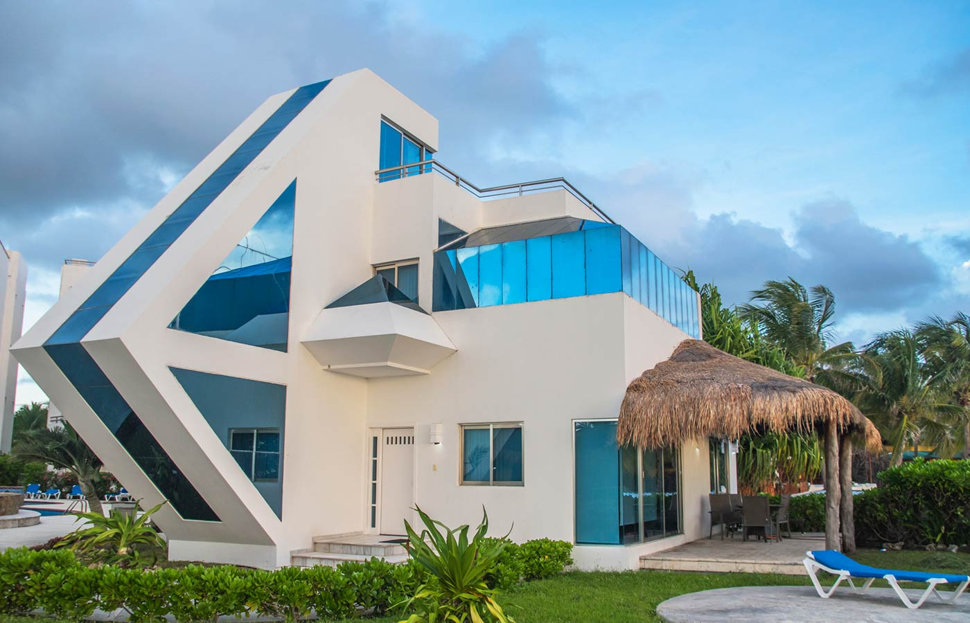 space age luxury villa surrounded by landscaped yard and palm trees