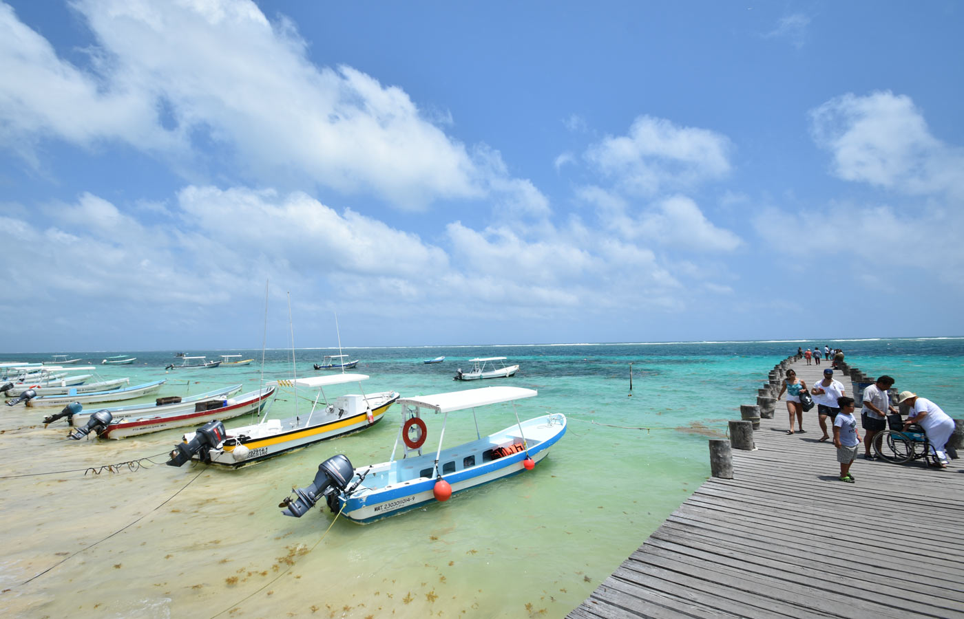 small boats anchored on the beach as people stroll up and down the pier