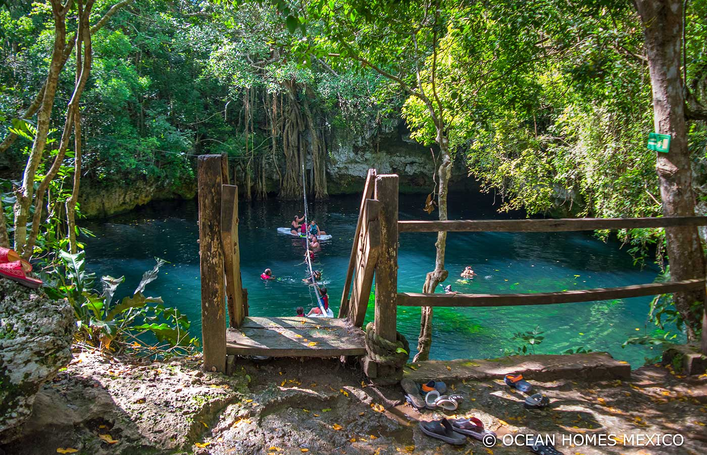 a rough hewn wooden ladder leads down into the blue green waters of a jungle cenote near puerto morelos. People can be seen swiming, rafting, and using a zip line