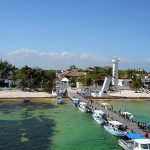 A dock stretches out onto the emerald ocean aside the leaning lighthouse of puerto morelos